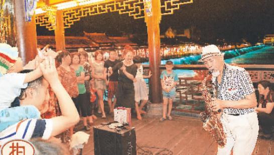先生和妻子表演萨克斯演奏,引来市民围观-58岁街头艺人被逐 引异图片