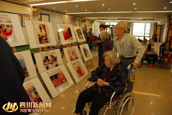 老人正在认真观看非遗知识展板(图片来自四川新闻网)