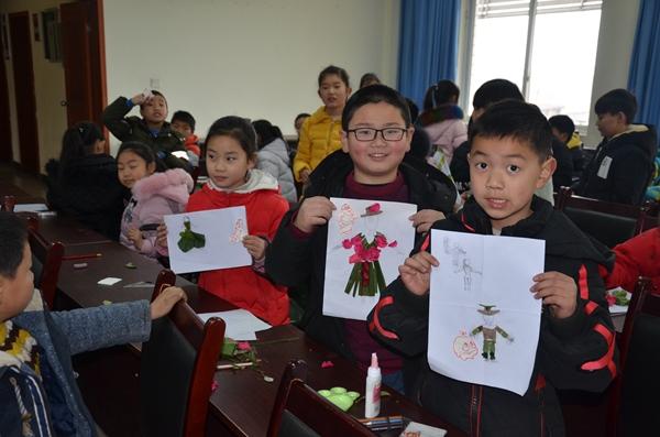 曹静老师从规范孩子们画画的姿势入手,在黑板上为同学们做好绘图示范